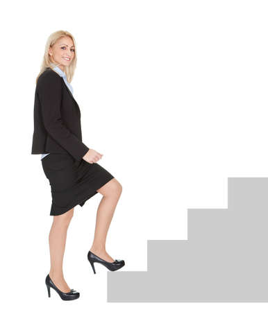 levels: Sucessful businesswoman walking up a staircase. Isolated on white Stock Photo
