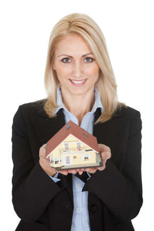 Businesswoman holding model of a house. Isolated on white photo