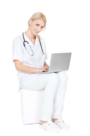 Medical doctor working on laptop. Isolated on white photo