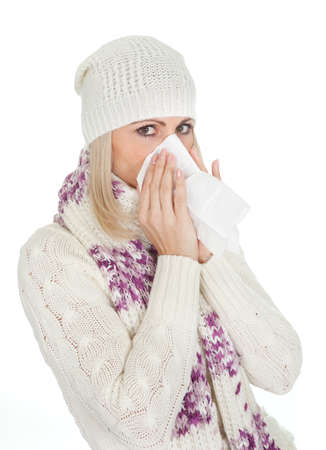 Woman in warm winter clothing sneezing from cold. Isolated on white photo
