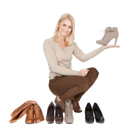 young feet: Beautiful young woomen choosing shoes to wear. Isolated on white