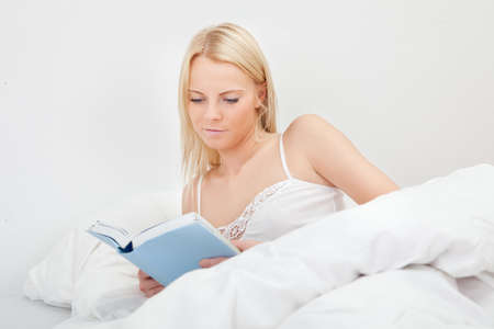 Young beautiful woman reading book photo