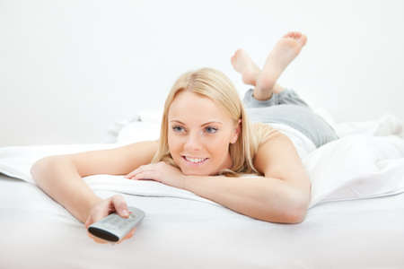 ver tv: Mujer hermosa joven acostada en la cama