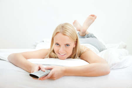 looking at watch: Young beautiful woman lying in bed Stock Photo
