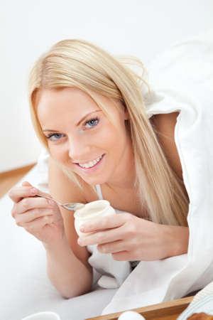 Beautiful woman eating yogurt in bed photo