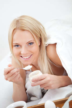 Beautiful woman eating yogurt in bed photo