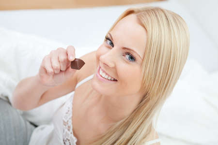 Beautiful woman eating chocolate photo