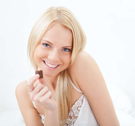 Beautiful woman eating chocolate photo