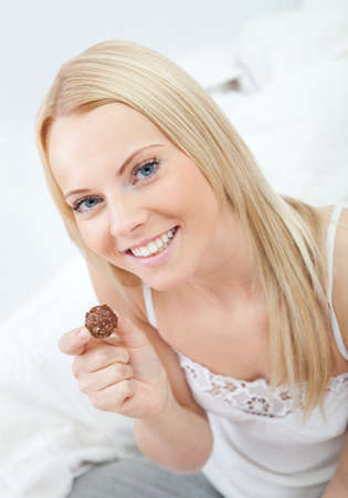 Beautiful woman eating chocolate Stock Photo - 12475518