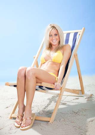 Beautiful young woman in bikini lying on a deckchair at the beach Stock Photo - 12475569