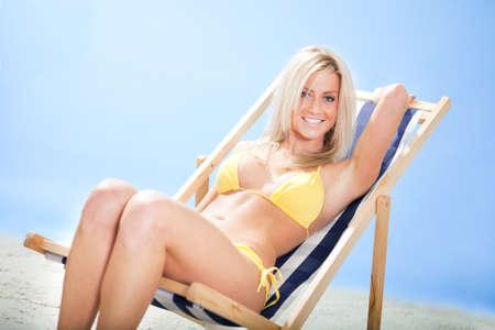 Beautiful young woman in bikini lying on a deckchair at the beach Stock Photo - 12475547