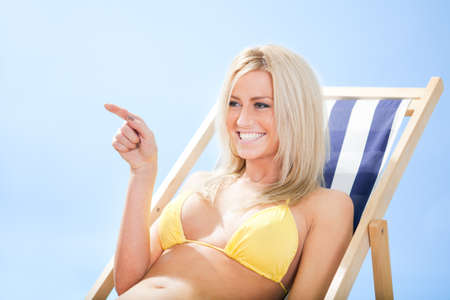 Beautiful young woman in bikini lying on a deckchair at the beach Stock Photo - 12475598