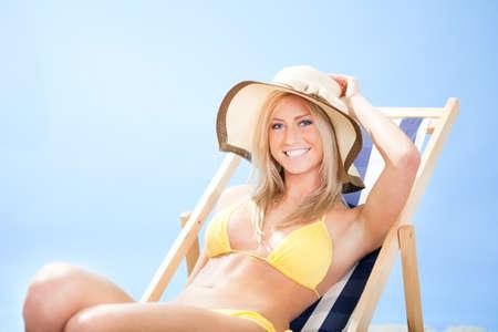 Beautiful young woman in bikini lying on a deckchair at the beach Stock Photo - 12475599