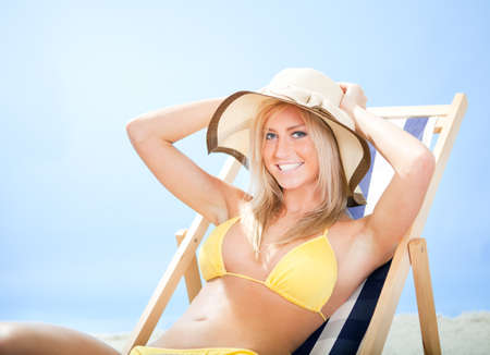 Beautiful young woman in bikini lying on a deckchair at the beach Stock Photo - 12475576