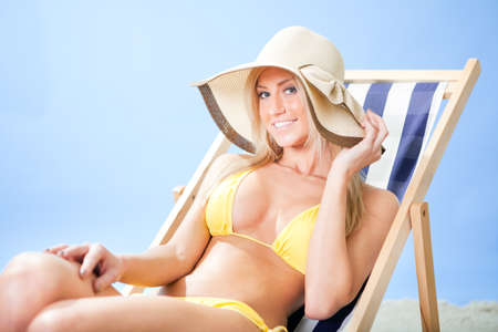Beautiful young woman in bikini lying on a deckchair at the beach photo