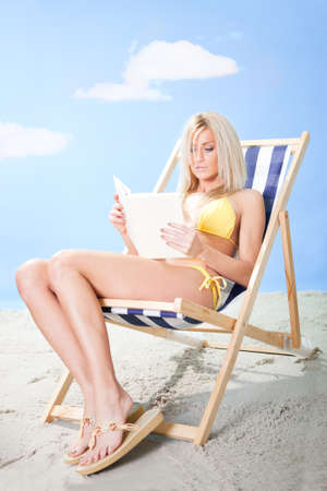 Beautiful young woman in bikini lying on a deckchair and reading a book at the beach photo
