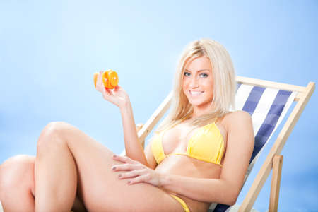 Beautiful young woman in bikini lying on a deckchair applying suncream at the beach photo