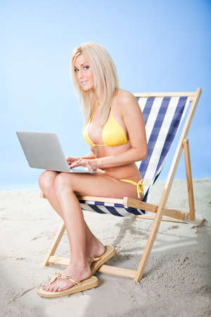 Beautiful young woman in bikini lying on a deckchair using laptop at the beach photo