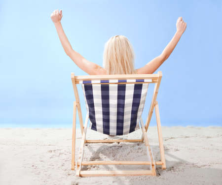 arms on chair: Beautiful young woman in bikini lying on a deckchair at the beach