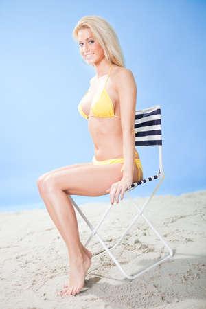 Joven y bella mujer en bikini sentada en una tumbona en la playa