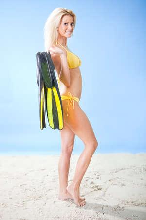 Beautiful young woman in bikini with snorkel equipment at the beach photo