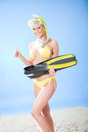 Beautiful young woman in bikini with snorkel equipment at the beach photo
