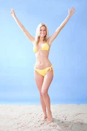 raised arms: Beautiful young woman in bikini at the beach