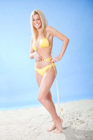 Beautiful young woman in bikini measuring waist at the beach photo