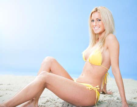 Beautiful young woman in bikini sitting on the send at the beach photo