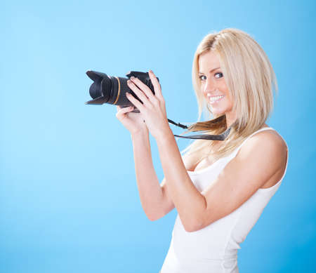 Portrait of beautiful young woman with camera on sky background photo
