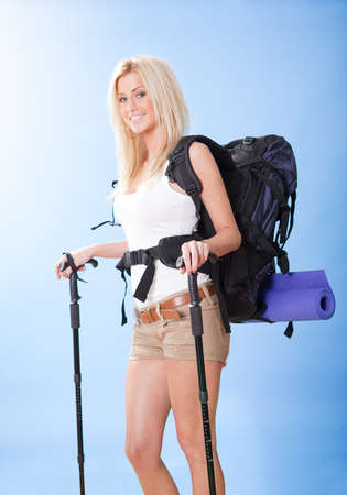 Beautiful young hiking woman with backpack and jogging sticks photo