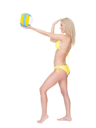 Beautiful young woman in bikini playing volleyball. Isolated on white photo