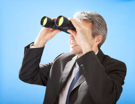 Portrait of successful senior businessman looking through binoculars on sky background photo