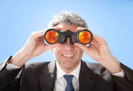 Portrait of successful senior businessman looking through binoculars on sky background Stock Photo - 12983575