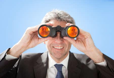 Portrait of successful senior businessman looking through binoculars on sky background Stock Photo - 12983575