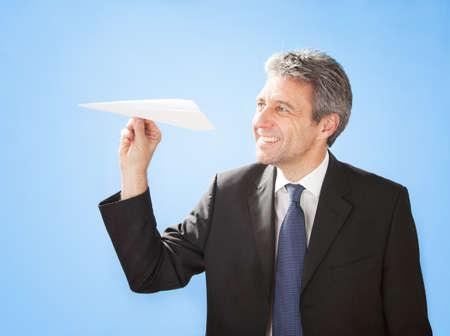 Portrait of successful senior businessman launching a paper plane Stock Photo - 12983581