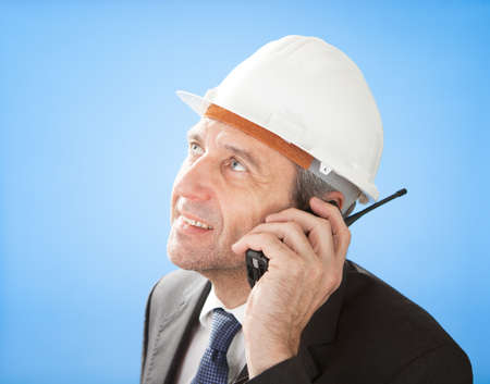 Portrait of senior architect talking on walkie-talkie at construction photo