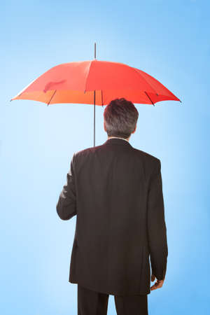 red umbrella: Portrait of senior businessmen holding a umbrella.