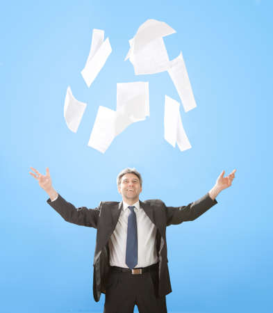 Portrait of senior businessman throwing sheets of paper into the air photo