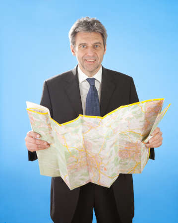 Portrait of senior business man looking into map for directions photo