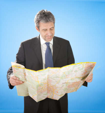 Portrait of senior business man looking into map for directions Stock Photo - 12983533