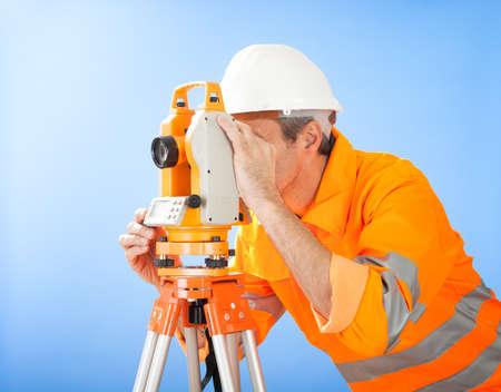Portrait of Senior land surveyor working with theodolite at construction site photo