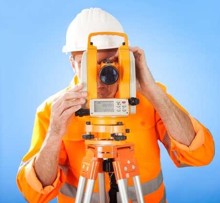 topografo: Retrato de agrimensor Superior trabajando con teodolito en el sitio de la construcci�n