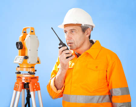talkie: Portrait of Senior land surveyor working with theodolite at construction site