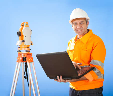 Portrait of Senior land surveyor working with theodolite at construction site Stock Photo - 12983559