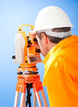 teodolito: Retrato de agrimensor Superior trabajando con teodolito en el sitio de la construcción