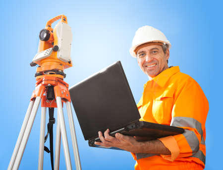 Portrait of Senior land surveyor working with theodolite at construction site photo