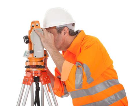 topógrafo: Retrato de agrimensor Superior trabajando con teodolito. Aislado en blanco