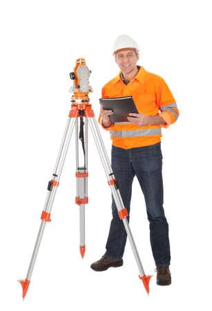surveyor: Retrato de agrimensor Superior trabajando con teodolito. Aislado en blanco