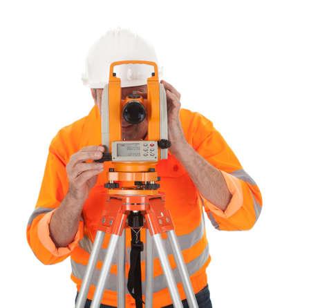 teodolito: Retrato de agrimensor Superior trabajando con teodolito. Aislado en blanco